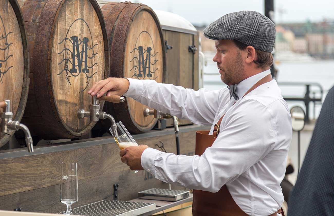 male pouring beer from barrel