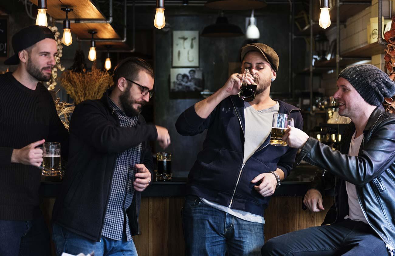 males enjoying dark brew beer